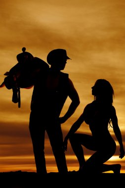 silhouette of woman down low look up at cowboy