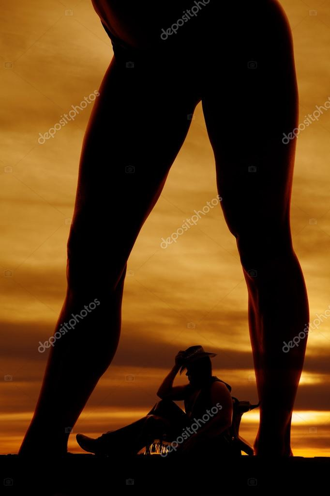 silhouette of woman in bikini bottoms legs over cowboy