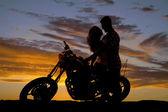 Silhouette Paar küsst sich auf Motorrad