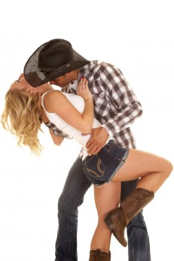 Cowboy getting ready to kiss woman's neck.