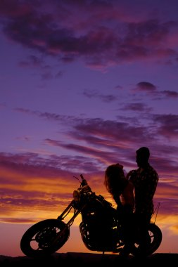 silhouette couple together on motorcycle her lean back