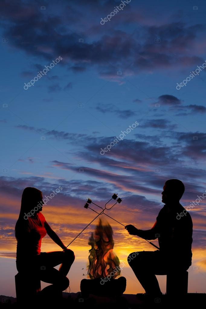 silhouette man and woman hold up marshmallows