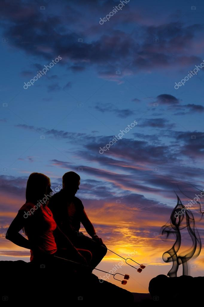 silhouette man and woman roasting some marshmallows on fire