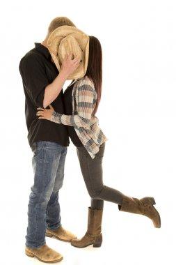 couple kiss behind hat leg up