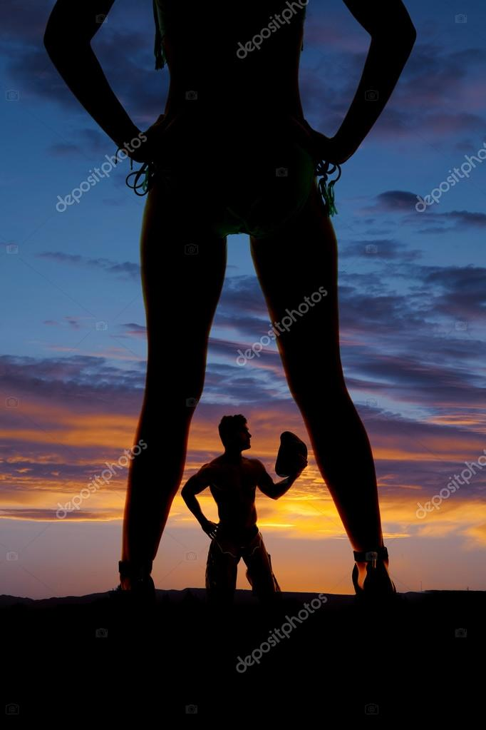 Silhouette of cowboy between woman legs