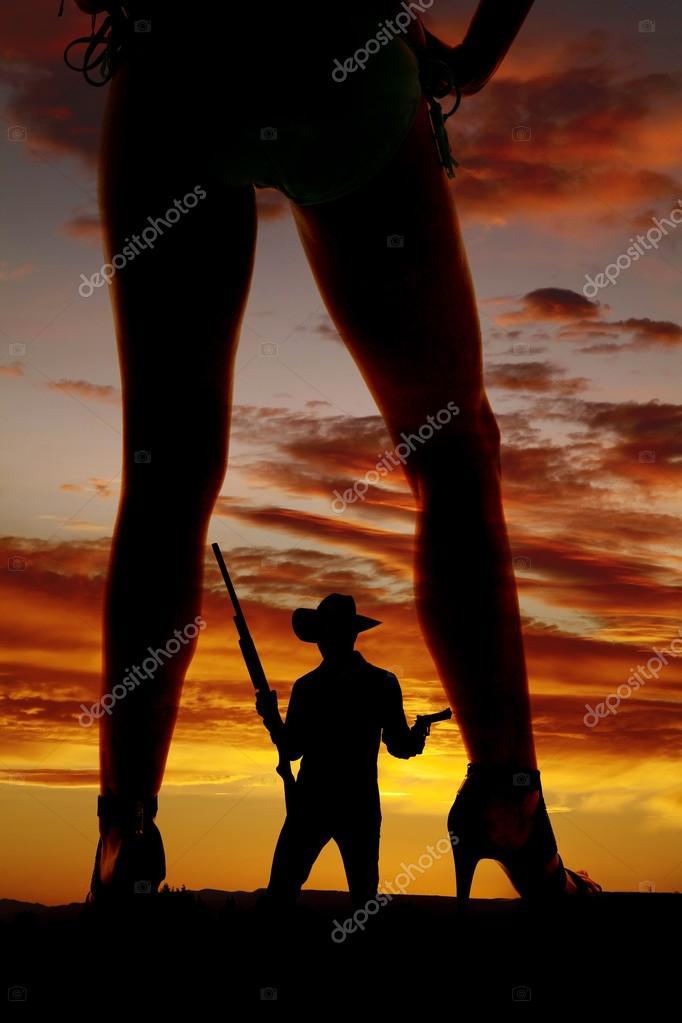 Silhouette of cowboy between woman legs