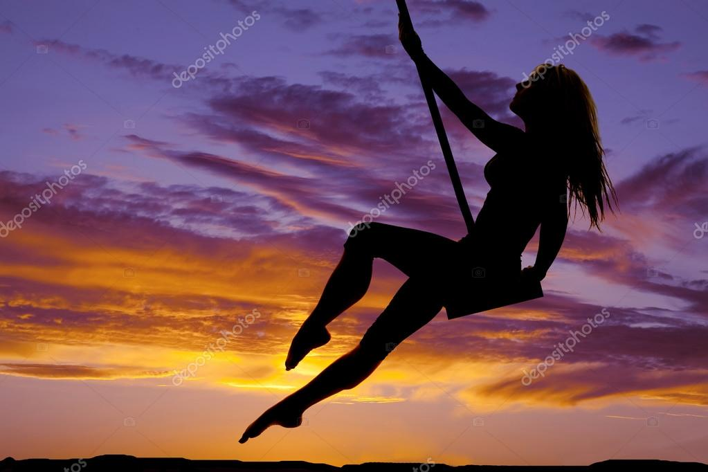 A silhouette woman swinging