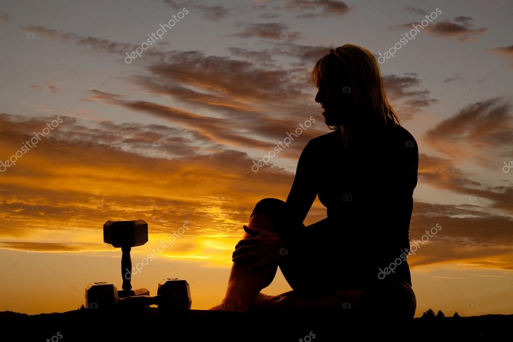 Silhouette woman sitting by weights