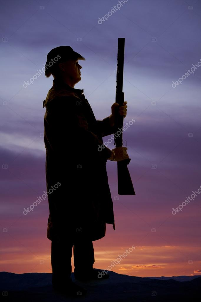 silhouette of cowboy in coat with gun upright