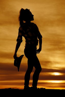 silhouette of a cowgirl holding her hat behind her looking up
