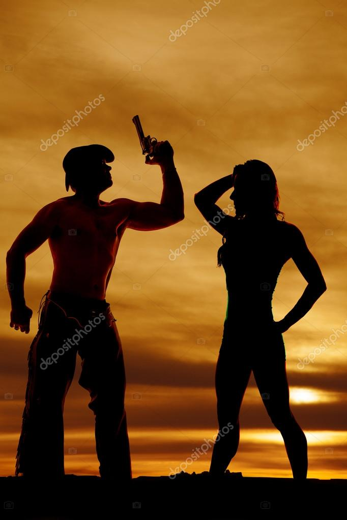 silhouette of cowboy with gun and woman
