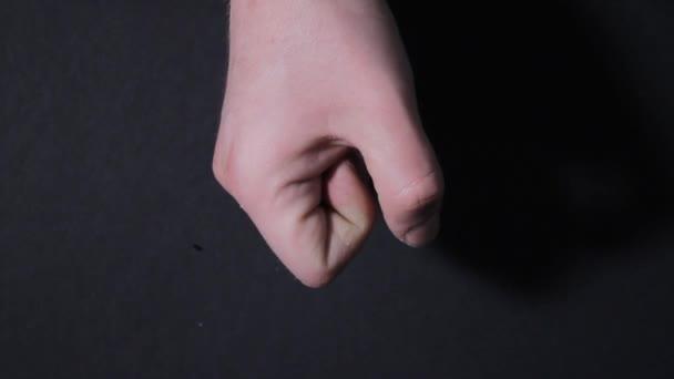 muž ruka sevře v pěst v hněvu na černém pozadí