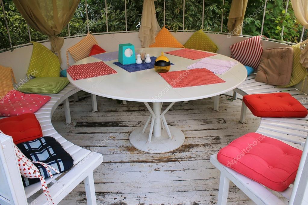 Zomer paviljoen met witte ronde tafel en veelkleurige kussens