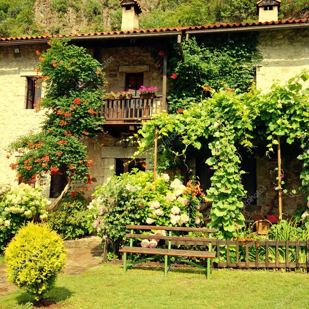 Rural house with blossom flowers in pretty cottage garden.