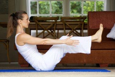 Yoga woman exercising by lifting legs