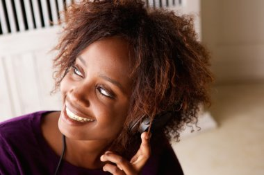 Smiling black woman listening to music