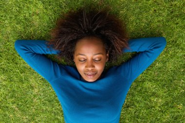 Young african woman lying on grass