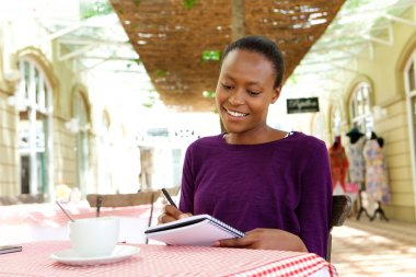 African woman writing in a cafe