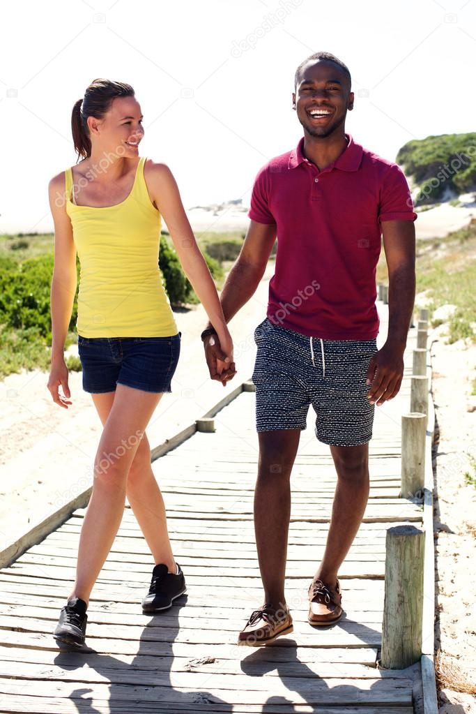 Happy young couple walking from the beach