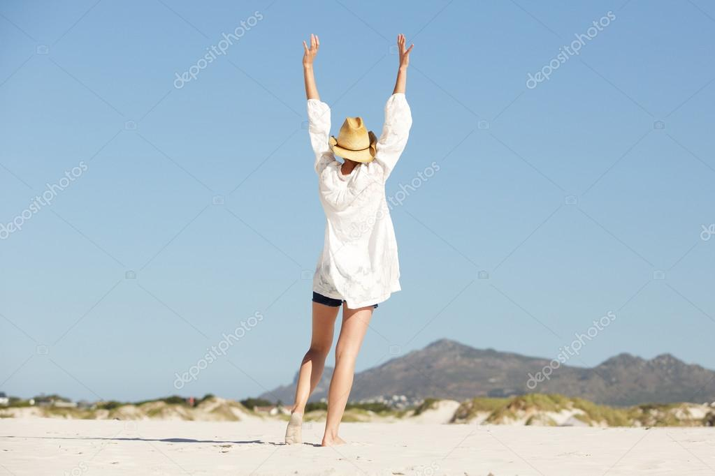 Young woman with raised arms walking on the beach