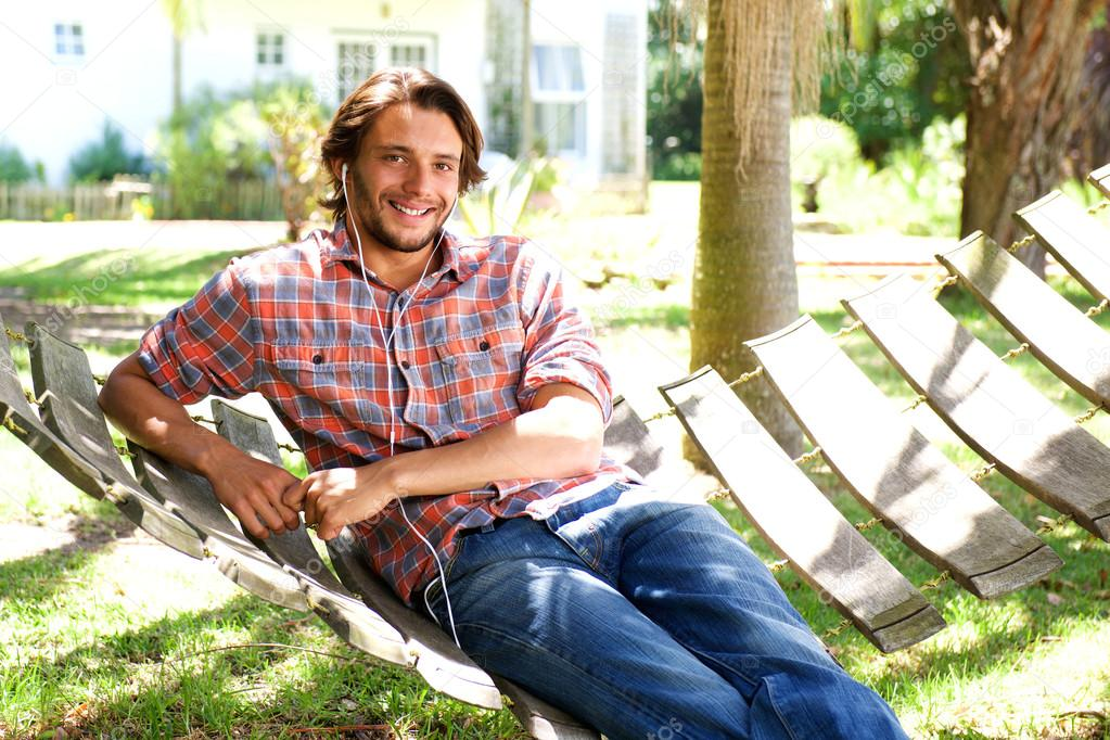 Young man lying in hammock with earphones