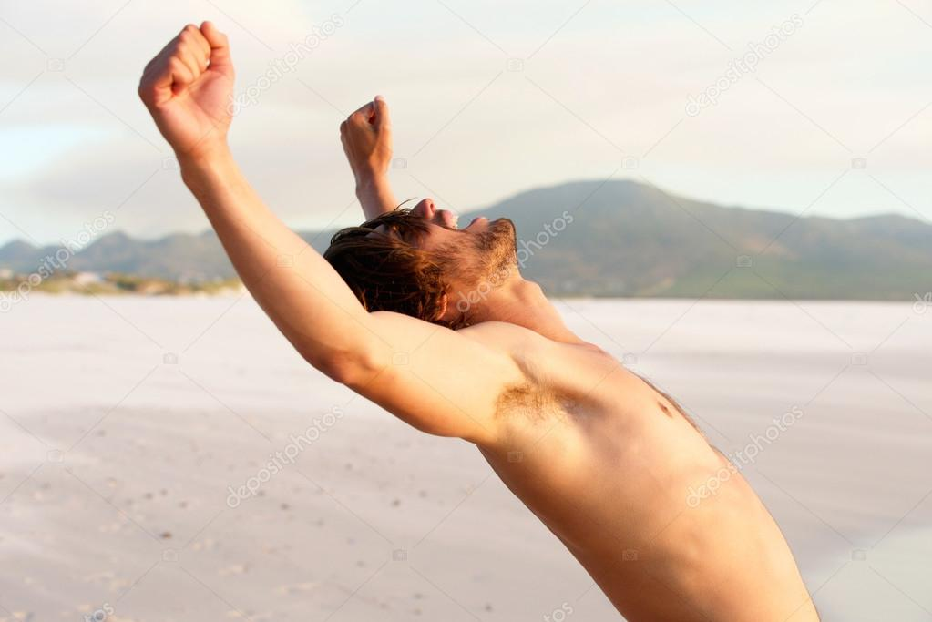 Shirtless young man with arms raised