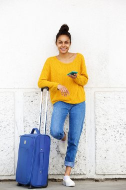 Woman with suitcase and mobile phone