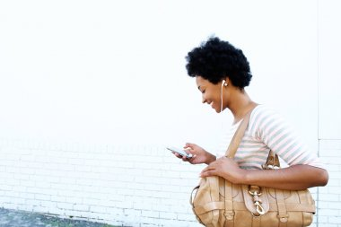 Smiling woman looking at playlist on cellphone