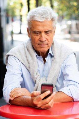 """Картина, постер, плакат, фотообои """"портрет седины мужчины, сидящего за столом и смотрящего на мобильный телефон постеры архитектур природа"""", артикул 470626580"""