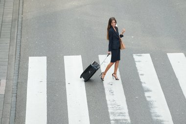 Business woman crossing street with travel bags