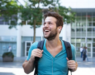 Happy young man listening to music on earphones