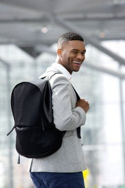 Young black man smiling with bag at airport
