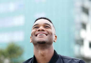 Cheerful young man laughing outdoors