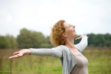 Cheerful carefree woman with arms outstretched