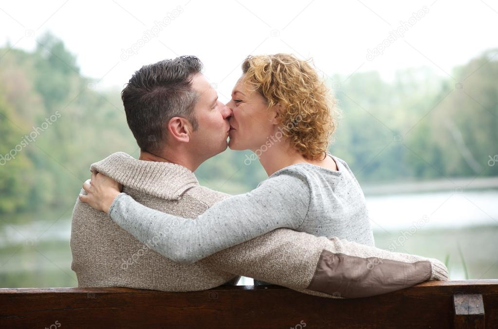 Happy couple kissing on park bench