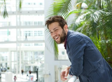 Happy man leaning inside bright building