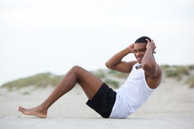 Healthy young man doing sit ups at the beach