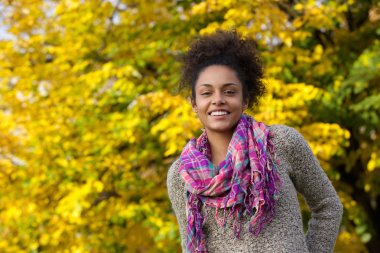 Beautiful young black woman smiling outdoors in autumn
