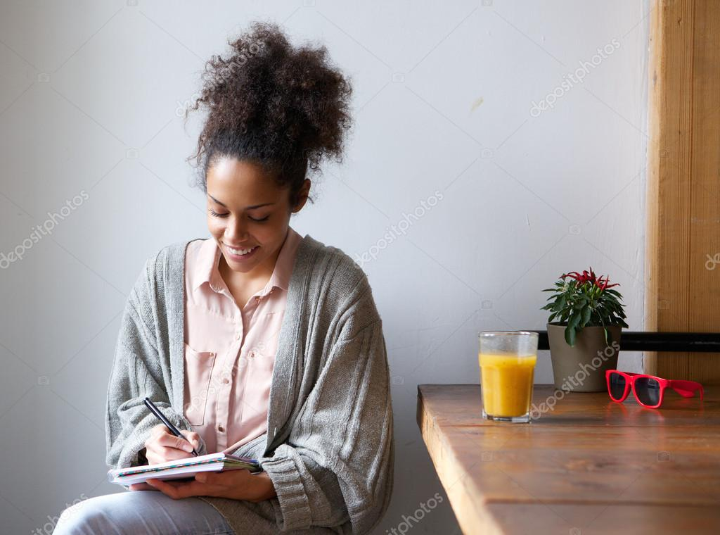 Smiling woman writing on note pad at home