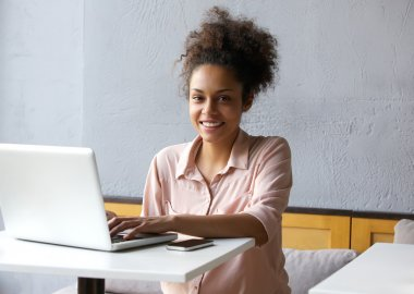 Smiling young black woman working on laptop