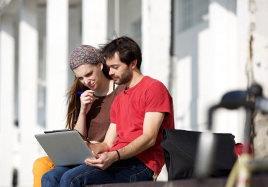 Two students sitting at campus looking at laptop together