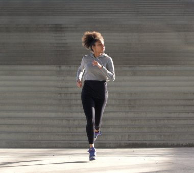 Young african american woman jogging alone outdoors