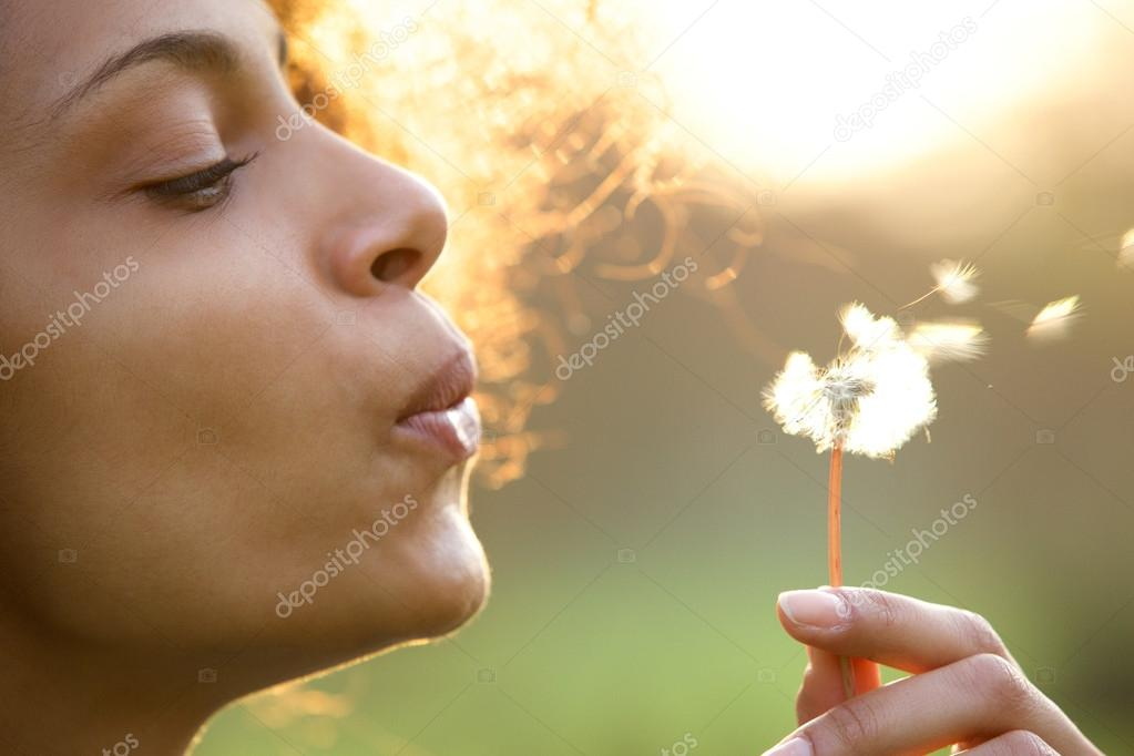 Beautiful young woman blowing dandelion flower