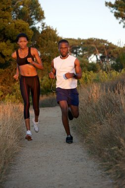 Healthy young black couple running together outdoors