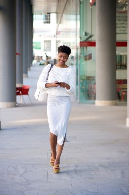 Smiling woman walking sending text message on cellphone