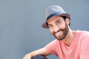 Close up portrait of a smiling young man with hat posing against gray background stock vector