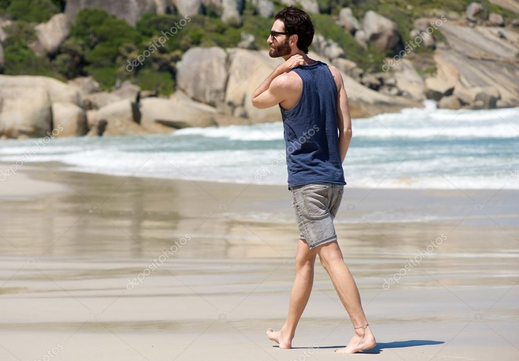 Handsome young man walking alone on empty beach