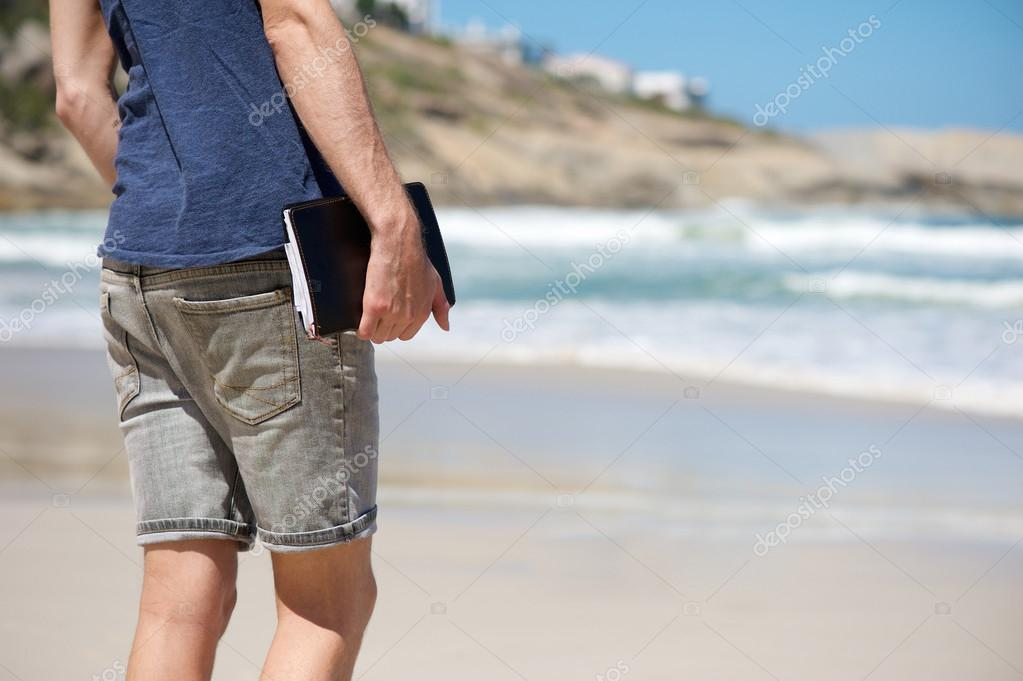 Man holding notebook while walking on the beach