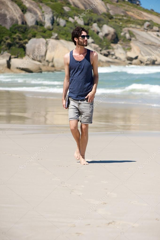 Happy man on vacation walking on isolated beach