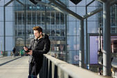 Šťastný muž čekající na stanici a při pohledu na mobilní telefon